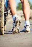 Los pies del ciclista y un neumático de la bici Foto de archivo