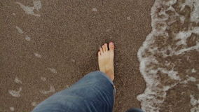 Los pies del hombre que caminan y que corriendo en la playa