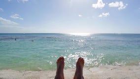 Los pies del hombre que se relajan por el océano en un día soleado con el cielo azul claro metrajes