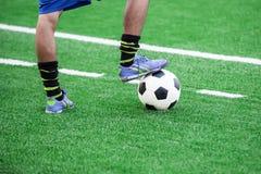 Los pies del jugador de fútbol que caminan sobre un balón de fútbol Imagen de archivo