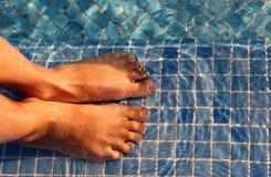 Los pies del muchacho se articulan y se ponen en agua Foto de archivo libre de regalías