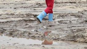 Los pies del niño caminan en la suciedad del charco, botas azules, inseguridad de los niños metrajes