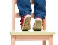 Los pies del niño que se colocan en la pequeña silla de puntillas Fotos de archivo libres de regalías