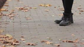 Los pies del otoño arrebatador del limpiador de calle parquean, persona que trabaja difícilmente para el salario bajo metrajes