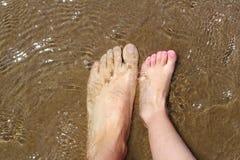 Los pies del padre y de los niños en la arena del verano varan Foto de archivo