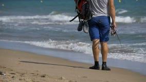 Los pies del pescador con cañas de pescar y una mochila caminan a lo largo de la playa de la orilla de mar Cámara lenta almacen de metraje de vídeo