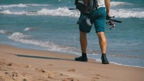 Los pies del pescador con cañas de pescar y una mochila caminan a lo largo de la playa de la orilla de mar Cámara lenta metrajes