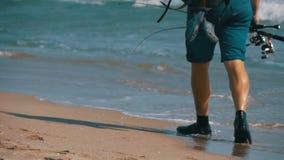 Los pies del pescador con cañas de pescar y una mochila caminan a lo largo de la playa de la orilla de mar Cámara lenta almacen de video