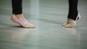Los pies del primer de bailarinas en pointe realizan elementos del ballet de la danza y diversos ejercicios en gimnasio del depor