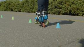 Los pies del rodillo de la mujer que montan conos redondos en parque almacen de video