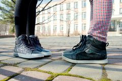 Los pies del ` s de los niños en botas grises están enfrente de uno a en el pavimento fotografía de archivo