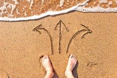 Los pies desnudos de los hombres en arena y flechas Fotos de archivo libres de regalías