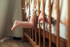 Los pies desnudos del bebé lindo pegan hacia fuera el pesebre Fotos de archivo libres de regalías