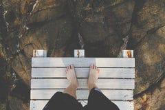 Los pies desnudos del hombre que se colocan en el muelle de madera Fotos de archivo libres de regalías