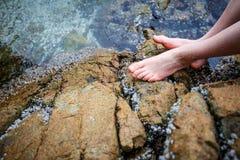 Los pies desnudos del muchacho en la roca Imagenes de archivo