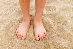Los pies desnudos del niño en arena Imagen de archivo libre de regalías
