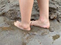 Los pies desnudos en la arena, friegan sus pies fotografía de archivo libre de regalías