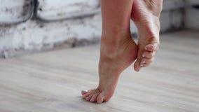 Los pies desnudos femeninos del ` s calientan colocando y moviendo encendido la extremidad de dedos del pie en piso de madera metrajes