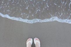 los pies en las chancletas blancas en la playa con la agua de mar agitan Fotografía de archivo