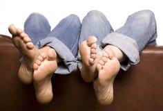 Los pies encima mueven hacia atrás del sofá Fotografía de archivo libre de regalías