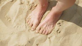 Los pies están en la arena cerca del agua Playa D?a asoleado del verano metrajes