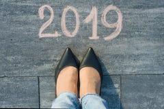 Los pies femeninos con la flecha y mandan un SMS a 2019 escrito en el asfalto Fotos de archivo
