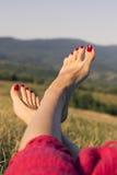 Los pies femeninos con los clavos rojos en el fondo de las montañas Fotografía de archivo