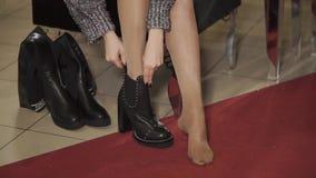 Los pies femeninos desnudos en una tienda de zapatos, muchacha están intentando en las botas, primer almacen de metraje de vídeo