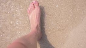 Los pies femeninos en la arena, la onda del mar cubren las piernas femeninas 4k, c?mara lenta almacen de video