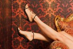 Los pies femeninos en sandalias están en silla Fotografía de archivo libre de regalías