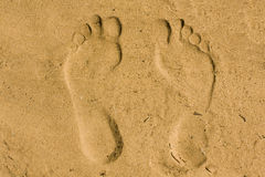Los pies imprimen en arena Fotos de archivo