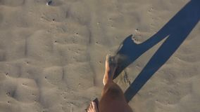 Los pies masculinos caminan a lo largo de la arena almacen de video