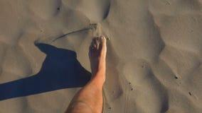 Los pies masculinos caminan a lo largo de la arena metrajes