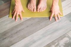 Los pies masculinos del entrenamiento de la aptitud del deporte de la yoga dan la estera de la yoga fotos de archivo libres de regalías