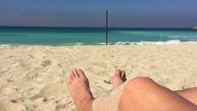 Los pies masculinos en la arena de la playa en el mar del fondo agitan el agua azul almacen de metraje de vídeo