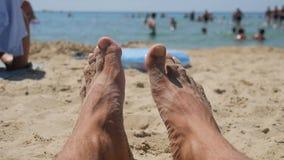 Los pies masculinos en una playa contra el mar en un día de verano, cierre para arriba, broncearon Vacaciones en el mar almacen de metraje de vídeo