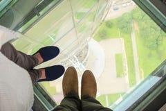 Los pies masculinos y femeninos en un piso de cristal en el Ostankino se elevan en Moscú, Rusia Fotografía de archivo libre de regalías