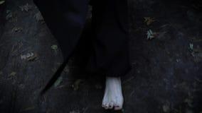 Los pies pálidos desnudos de la mujer están llevando la capa negra larga, caminando en bosque en otoño sobre la tierra mojada y l