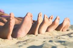 Los pies se relajan en la playa Imágenes de archivo libres de regalías