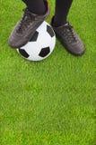 Los pies y el fútbol del jugador de fútbol Imágenes de archivo libres de regalías