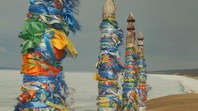 Los pilares con las cintas coloreadas son un símbolo religioso en el lugar sagrado de la isla de Olkhon en el lago Baikal metrajes