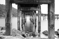 Los pilares de la foto blanco y negro del puente del puerto muestran los pilares viejos y el movimiento del agua Fotografía de archivo