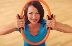 Los pilates mágicos suenan ejercicios del gimnasio del deporte de los aeróbicos de la mujer en el piso, sonriendo y mirando a la  Fotos de archivo libres de regalías