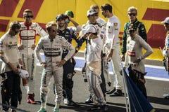 Los pilotos del Fórmula 1 recolectaron juntos en la línea de salida Imagen de archivo