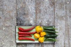 Los pimientos picantes verdes y amarillos rojos arreglaron en la bandeja Fotografía de archivo libre de regalías