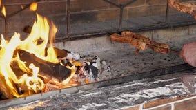 Los pinchos con kebabs se están poniendo sobre la parrilla para cocinar cerca de la llama grande almacen de video