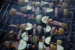 Los pinchos con las rebanadas de patatas, calabacín, tocino, setas, cebolla, colinabo asaron a la parrilla sobre los carbones de  Fotografía de archivo libre de regalías