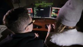 Los piratas informáticos de ordenador multiétnicos jovenes combinan cortar, intentando acceder a un sistema informático almacen de metraje de vídeo