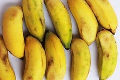 Los plátanos maduros se cortan juntos en un fondo amarillo Imagenes de archivo