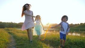 Los placeres de la familia, las muchachas preciosas con el niño pequeño en sombrero pasan feliz ocio con las cintas y los molinoe almacen de metraje de vídeo